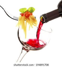 glass with red wine and forks with pasta on white background