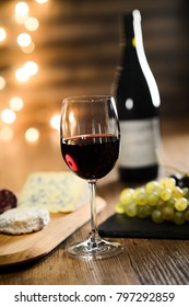 glass of red wine with french cheese and delicatessen in restaurant wooden table with romantic dim light and cosy atmosphere