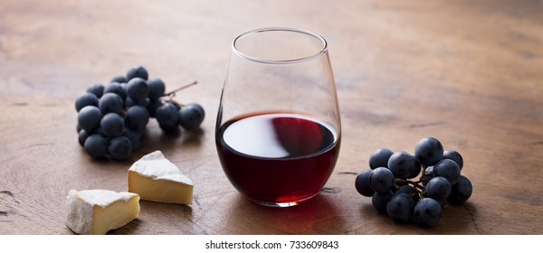Glass of red wine with fresh grape and cheese on wooden table.