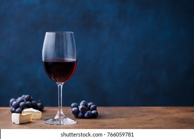 Glass of red wine with fresh grape and cheese on wooden table. Blue background. Copy space.