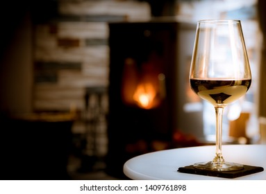 Glass of red wine in front of cosy fireplace