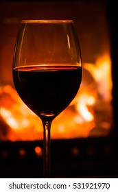Glass of red wine in front of a fireplace