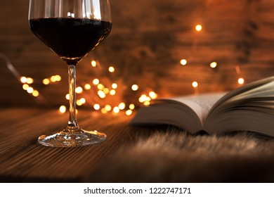 Glass of red wine with a good book and gold bokeh on a cozy winter evening
