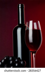 a glass of red wine grape and bottle