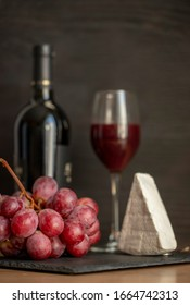 Glass of red wine with grapes and brie cheese on a wooden background. Red Wine bottle, brie cheese and  wineglass on black wood background, top view, copy space.