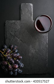 Glass of red wine and grapes on black slate stone board over dark background. Top view, copy space