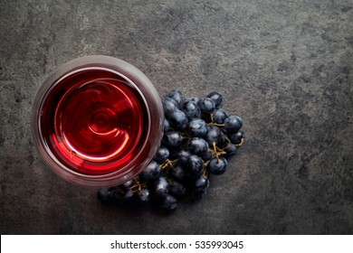 Glass of red wine and grapes on dark gray background from top view
