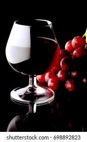 A glass of red wine with grapes on a dark background