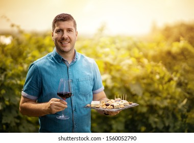 Glass of red wine in hand of a young winemaker in the vineyard - Wine tasting tour - Man welcoming tourist at sunset in the winery. Toned