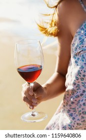 Glass of red wine in the hands of a girl against the backdrop of a coastline, close-up