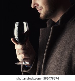 A glass of red wine holding by man wearing spring coat,  smelling red wine before tasting and drinking it. Low key portrait.