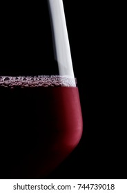 Glass of red wine macro with bubbles and reflection on black background