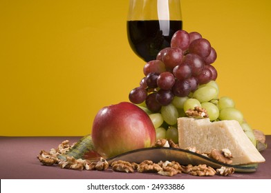 Glass of red wine with multicolored grapes, apple and cheese lying on color plate.