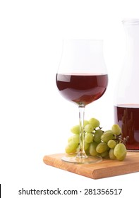 Glass of red wine next to a branch of white table grapes over the serving wooden board, composition isolated over the white background, framed as a copyspace background composition