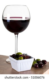 Glass of Red Wine With Olives on a Wooden Board