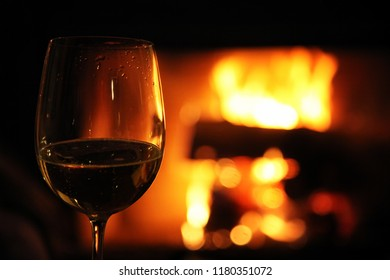 Glass with red wine on the background of fire in the fireplace, coziness and warmth at home