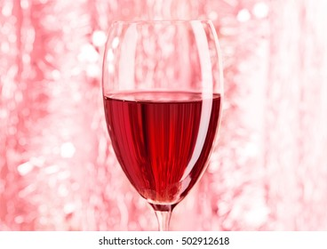 Glass of red wine on red bokeh background for celebration