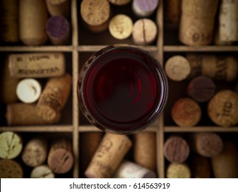 Glass of red wine on bottle corks in a wooden box, view from above