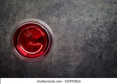 Glass of red wine on dark gray background from top view