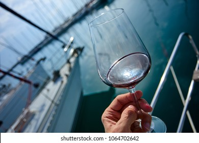 a glass of red wine on the deck of the yacht