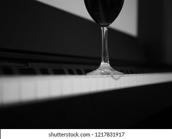 Glass of red wine on piano, black and white,