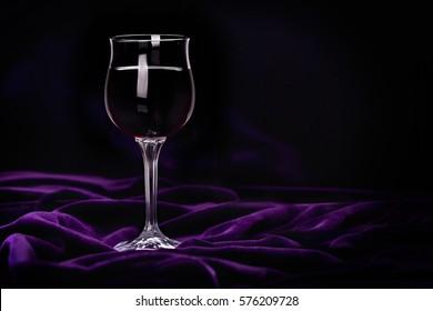 Glass of red wine on purple rippled velvet fabric. Romantic dinner concept.