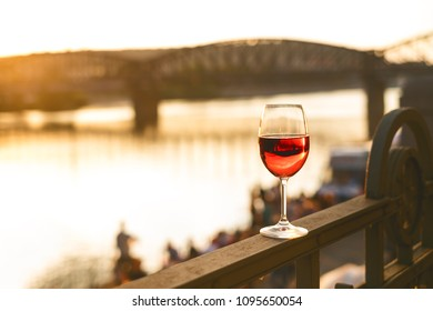 Glass of red wine on a railing with sunset in a Prague city. Concept of free time in the city and drinking alcohol.