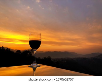 Glass of red wine on reflective table during sunset over Himalayan mountain range in Nepal