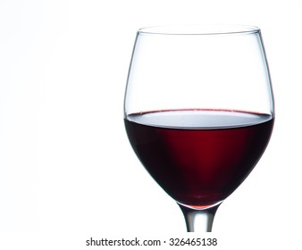 glass of red wine on the glass table and white background