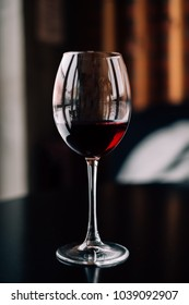 Glass of red wine on the wooden table in the bar