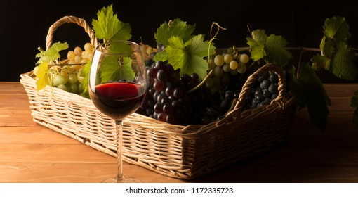 glass with red wine on the wooden table with a basket of grapes