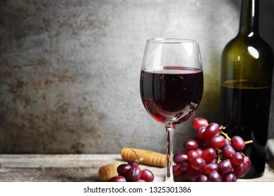 Glass of red wine on a wooden table in a rustic and vintage wine bar with grapes and a bottle of wine on background with copy space.