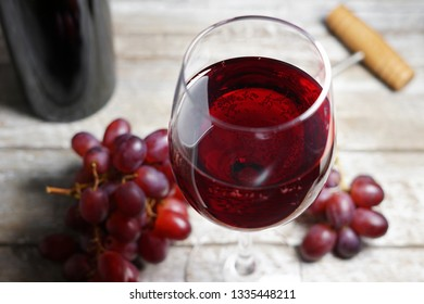 Glass of red wine on a wooden table in a rustic and vintage wine bar with grapes fruit and a bottle of wine on background closeup view.