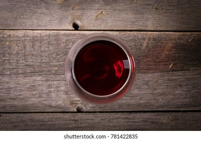 Glass of red wine on wooden table. View from top