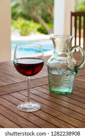 Glass of red wine in poolside. Refreshment on summer day