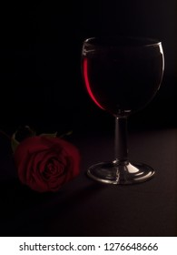 Glass of red wine and red rose on the table. Low key