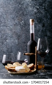 Glass of red wine served with cheese camembert, honey, jam and french baguette over dark texture background