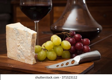 Glass of red wine served from an elegant decanter with fresh gorgonzola cheese and red and green grapes.