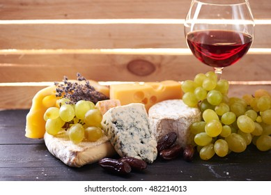 The Glass of red wine served with grapes, date fruits and the variety of cheese on a black wooden table with the wooden board on a background with a ray of light shining through it. Close view