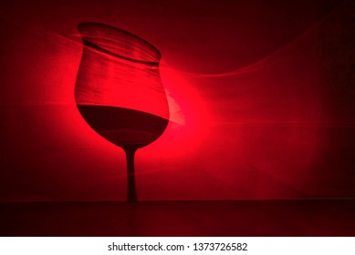 Glass of red wine as a shadow in red light