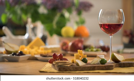 glass of red wine with a snacks stand on the wood table