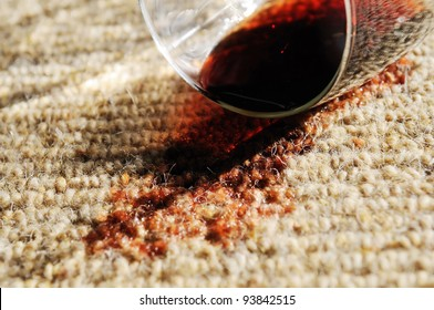 A glass of red wine spilt on a pure wool carpet.