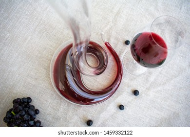 glass red wine and spiral shaped wine decanter  on the table covered beige cotton table cloth. top of view. bottle red wine.