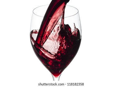 Glass of red wine splashing while being poured.Isolated on white.