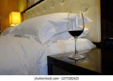 A glass with red wine stands on the bedside table. Bed with pillows and a lamp in the background.