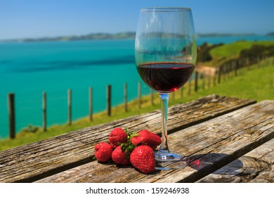 A Glass of Red Wine with Strawberry Standing on Old Table at the Beach on the Pacific Coast, Auckland, New Zealand