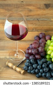 Glass of red wine with three kinds of grapes