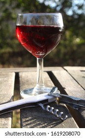 Glass of red wine with traditional Bistrot corkscrew in the foreground