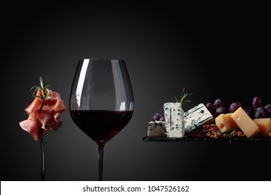 Glass of red wine with various cheeses , grapes and prosciutto on a black background.