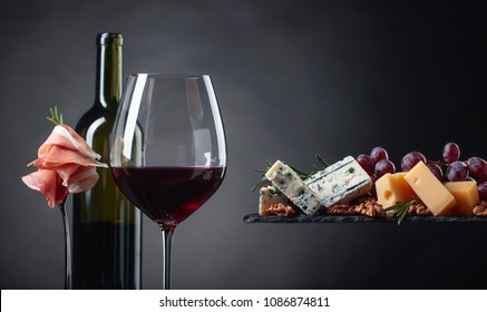Glass of red wine with various cheeses , fruits and prosciutto on a black background. Copy space .